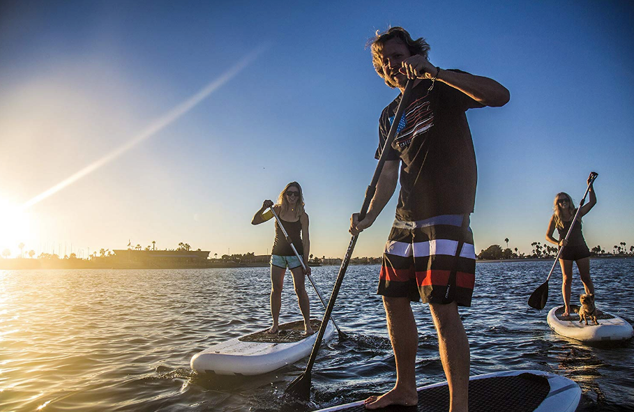 Three people, each on a paddle board, on a lake at sunset. Two are on an inflatable paddle board, the other is on an epoxy paddle board.