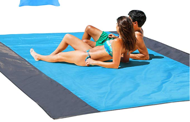 A couple enjoying the beach on their sand free mat, a must-have summer beach accessory.