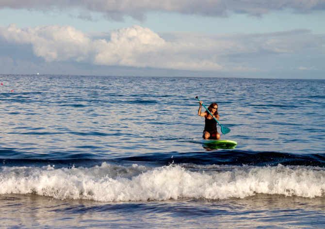 A woman paddleboarding on her knees in the ocean. It's okay to stay on your knees while paddleboarding instead of standing up.