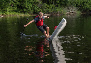 A young person falling off a paddle board into a lake. He's falling away from the board, which is safer than trying to fall on the paddle board.