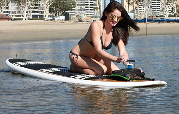 A woman on a paddle board pulling her phone out of the SUP-now paddle board pouch with waterproof insert.