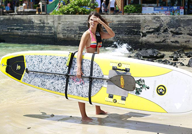 A woman holding a paddle board using the SUP-now paddle board carrier strap. The strap has a place to hold the paddle board paddle too.